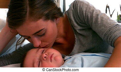 Mother lying with sleeping baby boy on bed in slow motion