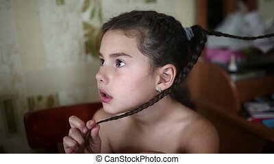 mother makes daughter female girl hair braid sitting in the...