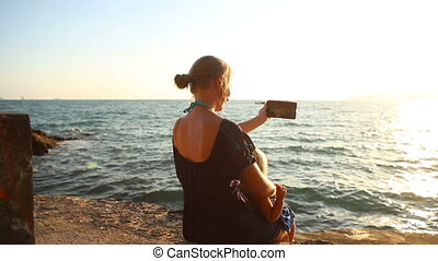 mother makes selfy with daughter sitting at sunset