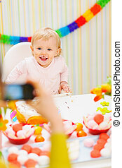 Mother making photos of baby on birthday party