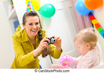 Mother making photos of babys first birthday