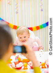 Mother making photos of happy baby on first birthday party
