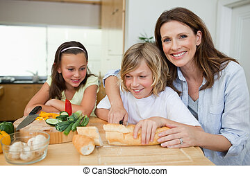 Mother making sandwiches with her children