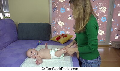 Mother massage her little baby daughter legs on bed