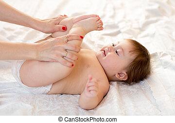 Mother massaging her baby girl