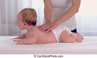 Mother massaging her little baby. Happy mother playing with...
