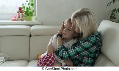 Mother measuring temperature of her ill kid at background. Sick child with high fever lying at sofa at home