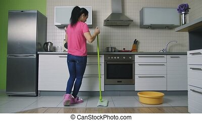 Mother mopping the floor and dancing holding baby