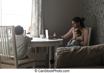 Mother multi-tasking work and children - Young mother...