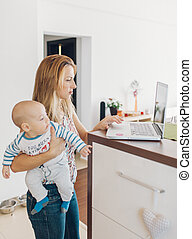 Mother navigating the internet with baby in arms