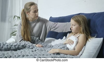 Mother nursing her ill daughter in bed at home