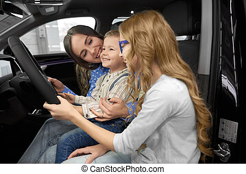 Mother observing new car with children in car cabin.