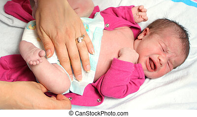 changing diaper - mother of a newborn baby girl changing...