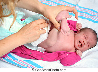 changing diaper - mother of a newborn baby girl changing ...