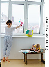 Mother of a toddler boy is cleaning plastic window door with scrubber