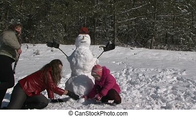 Mother of squatting alongside daughter and snowman and smile