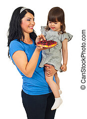 Mother offering tart fruit to her daughter