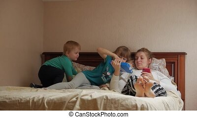 Mother on the bed with children with smartphone