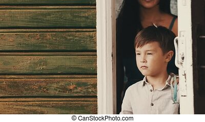 Mother open door walk out from country house with son....