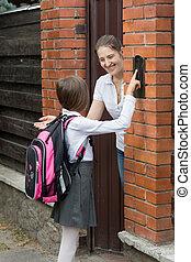 Mother opening door to her daughter that came from school
