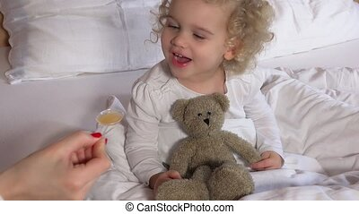 Mother or doctor give happy toddler girl spoon with medicine...
