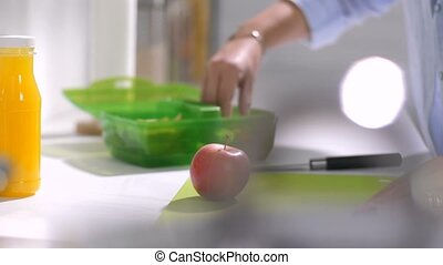 Mother packing meal for school lunch into box - Closeup of...