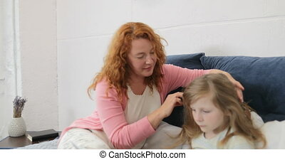 Mother Petting Daughters Head While Girl Using Laptop Computer, Family Sitting On Bed In Bedroom Spend Time Together