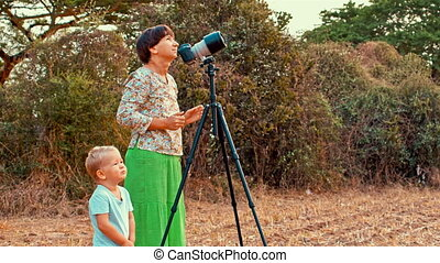Young woman takes pictures with camera on tripod accompanied with her toddler son