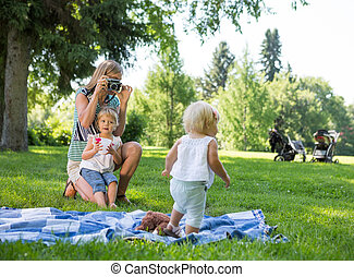 Mother Photographing Daughter In Park