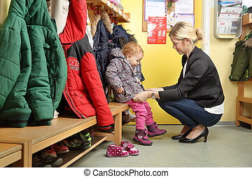 Mother picking up her child from a Kindergarten in wardrobe ...