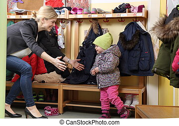 Mother picking up her child from a Kindergarten in wardrobe