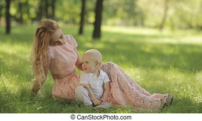 Mother Play With Her Child In A Park On The Grass