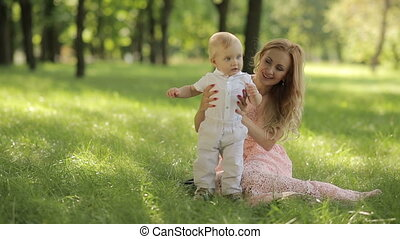 Mother Play With Her Child On The Grass