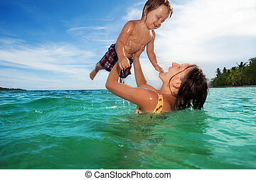 Mother play with her son in the sea