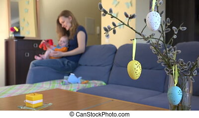 Mother play with little baby  on couch in living room. 4K