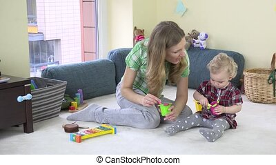 mother play with little girl with toy spoon pot in room. 4K