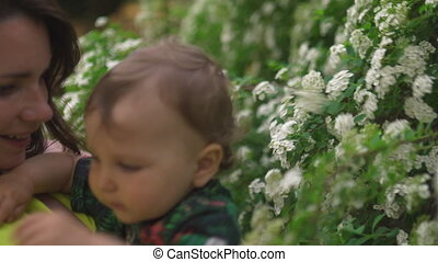 Mother playing and talking to baby child boy with flower blossoming tree in the background - Young mom in green dress and her baby in a green park having fun - Happy smiling people