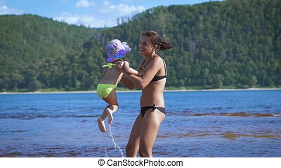 Mother playing turning around her baby girl daughter in the lake