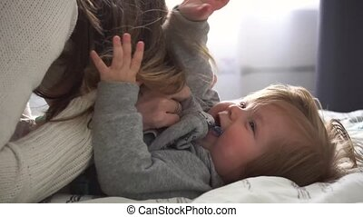 Mother playing with baby girl and she laughing