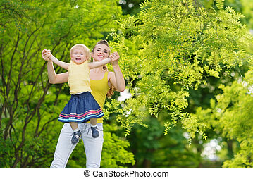 Mother playing with baby girl outdoors