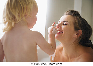 Mother playing with baby in bathtub
