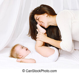 Mother playing with baby in bed at home