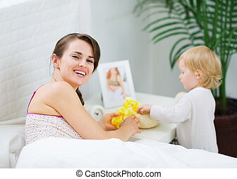 Mother playing with baby in bedroom