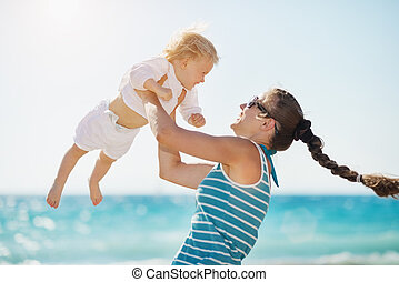 Mother playing with baby on beach