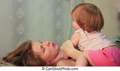 mother playing with baby on bed