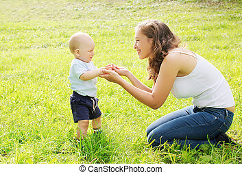 Mother playing with baby on the grass in summer day