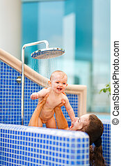 Mother playing with baby while taking shower