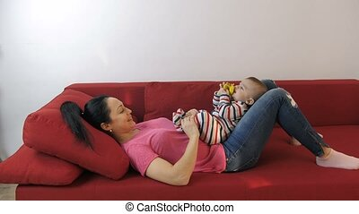 Mother playing with baby's feet lying on sofa