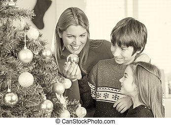 Mother playing with children with Christmas balls and tree
