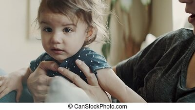 Mother playing with daughter at home on the couch. Real life, candid footage. Shot in 4K RAW on a cinema camera.
